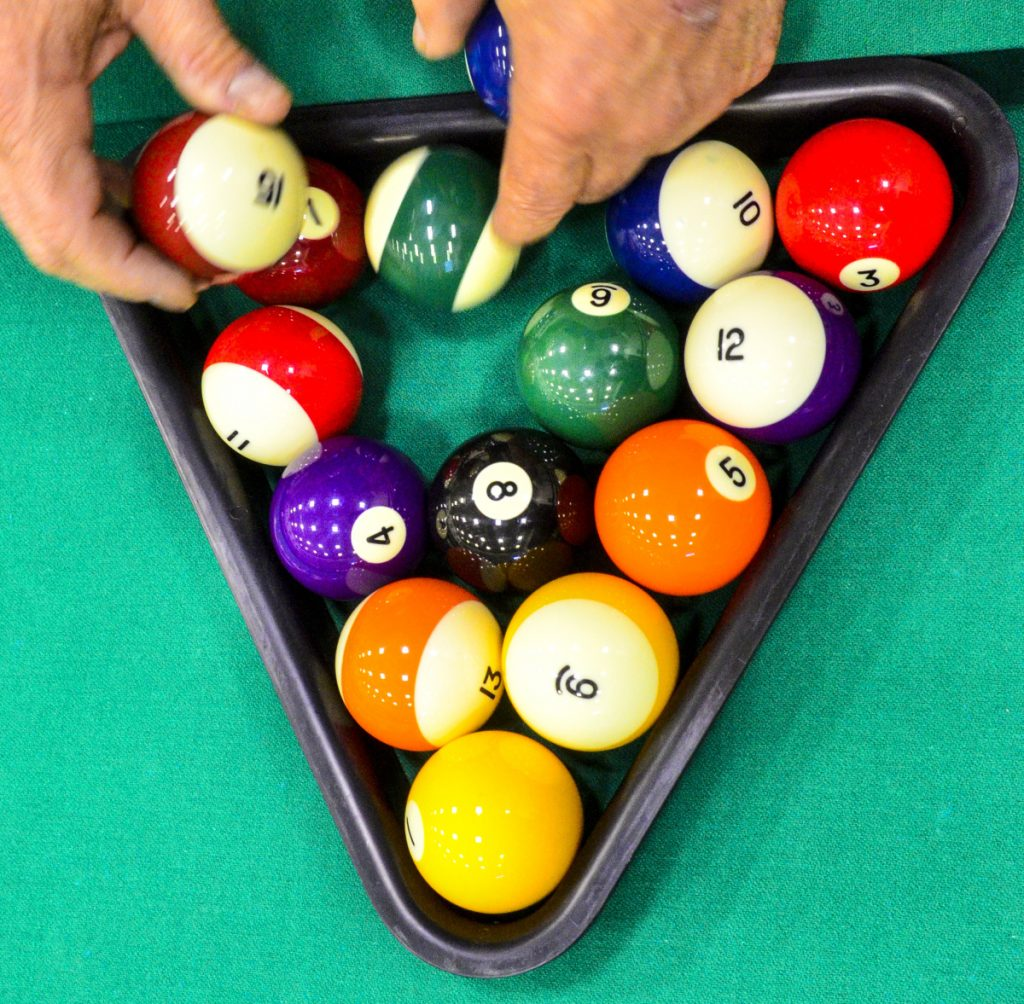 A competitor racks balls to start another round during a pool tournament on Sunday in the Augusta Armory.