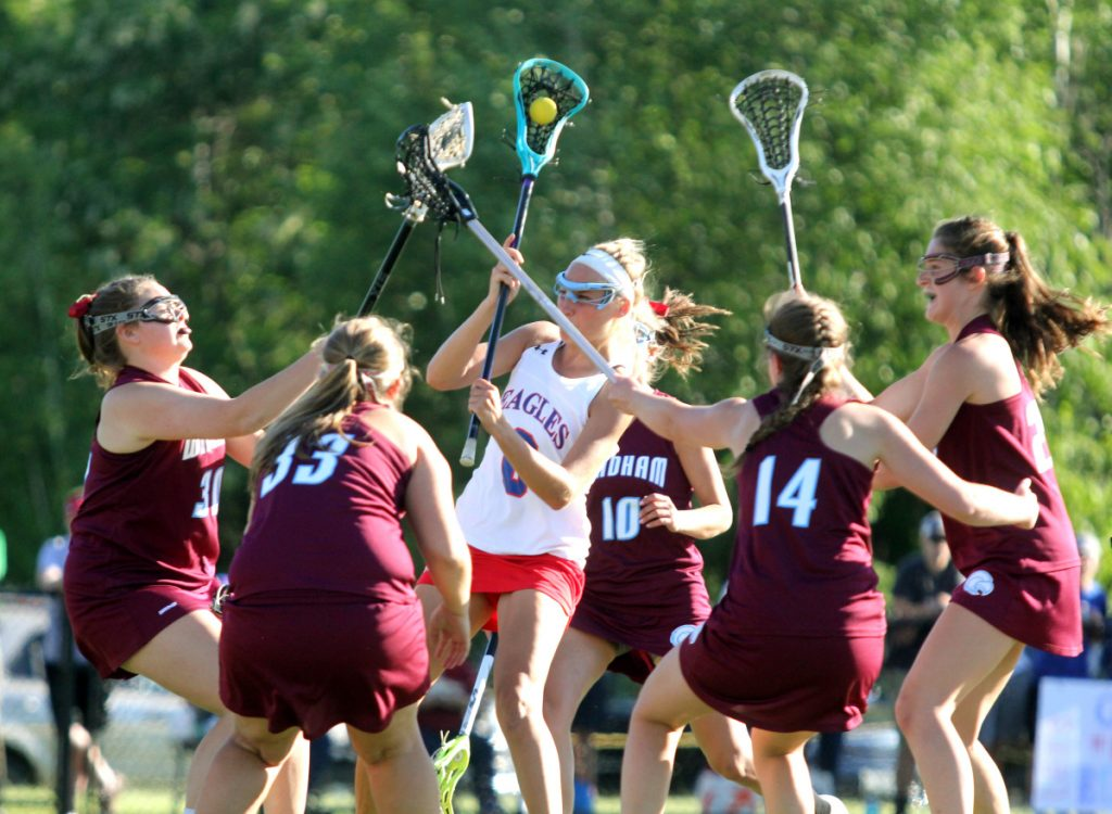 Messalonskee's Ally Turner tries to get a shot off as a host of Windham defenders converge in the first half of the Class A North championship game last season at Thomas College. With athletes becoming faster and stronger and the sticks flying throughout the game, more girls are starting to wear helmets.