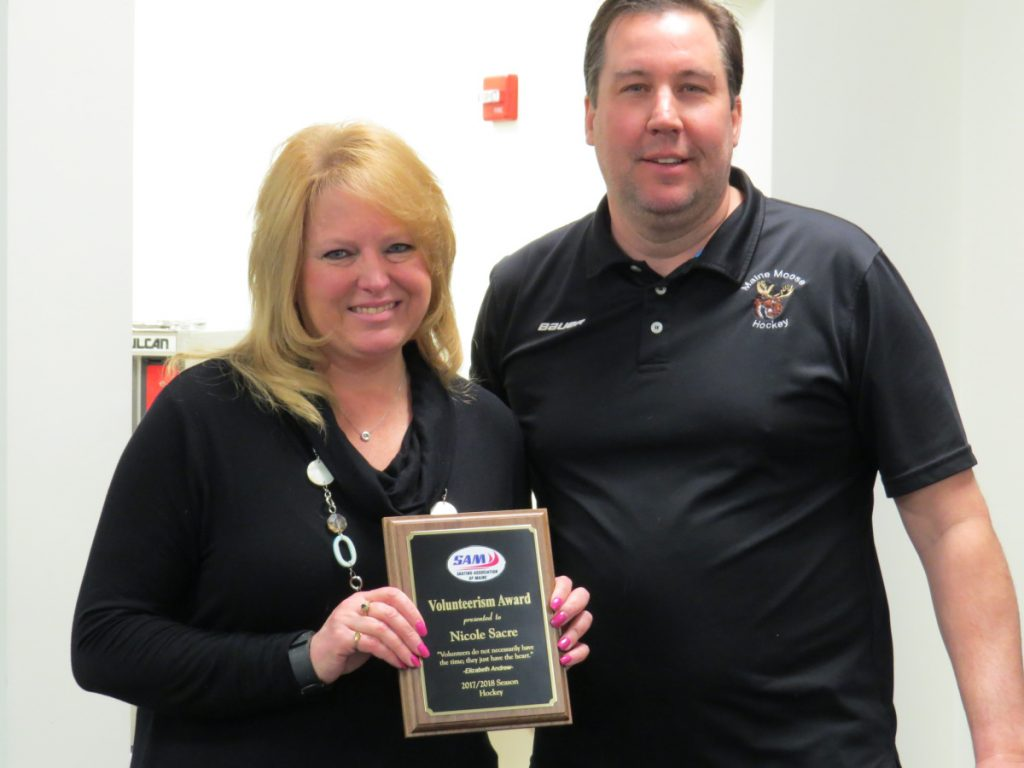 An outstanding volunteerism award was presented to SAM registrar Nicole Sacre, left, from Pittston, by Dan Foster, chair of the hockey committee during the annual meeting at the Camden National Bank Ice Vault in Hallowell.