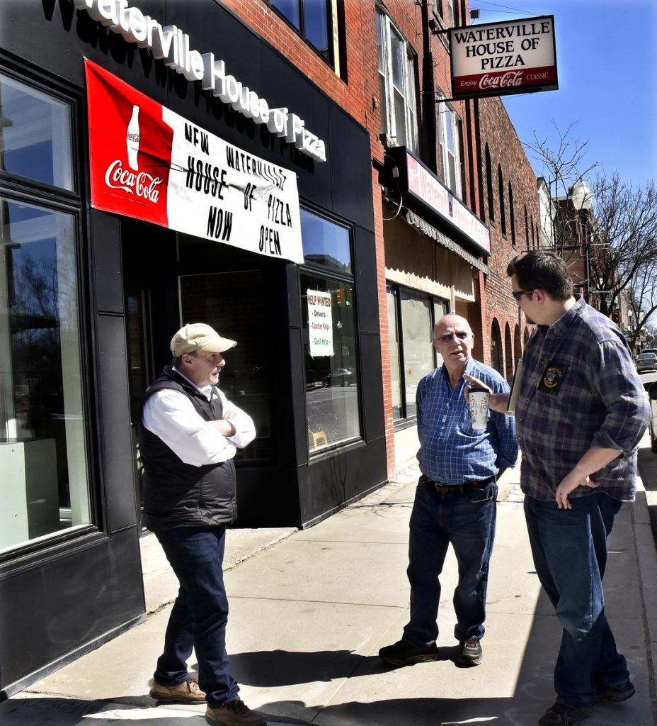 Waterville House of Pizza owner Stavros Kosmidis, center, speaks with Waterville Code Enforcement officer Dan Bradstreet, right, and Mark McCluskey outside his new restaurant beside the former location on Main Street in Waterville on Monday.