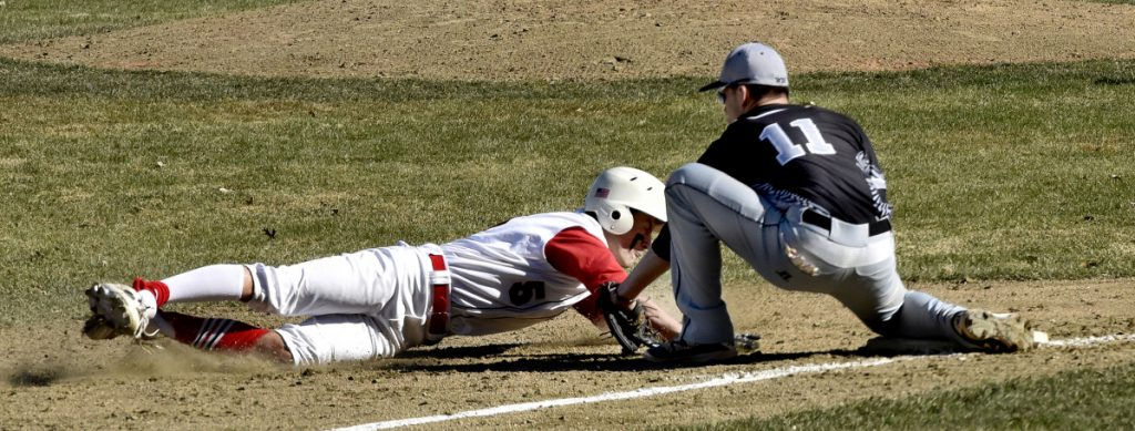 Bridgeway's Eric Wescott (11) attempts to tag out Hall-Dale's Austin Stebbins at third base during a Mountain Valley Conference game Monday in Farmingdale.