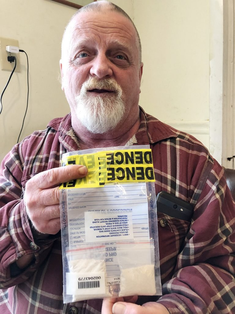 Kevin Curtis holds an evidence bag Tuesday that contains two clear pouches filled with the ashes of his late father, Robert C. Curtis Sr. The smaller bags had been seized as suspected heroin by Kennebec County sheriff's deputies after a car crash Saturday in Manchester. Kevin Curtis had lent his car to a friend to go to the grocery store, and the remains were in the glove box.