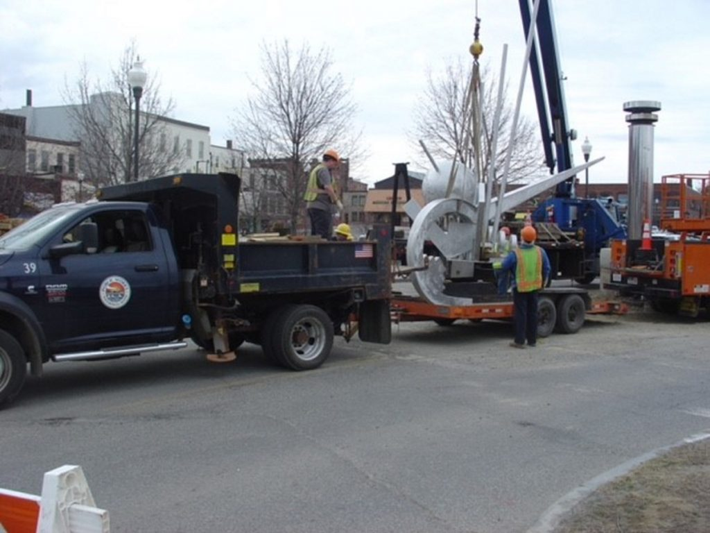 "Members of a Waterville public works crew secure the crown of ""The Ticonic"" sculpture on a trailer. The top part of the sculpture was taken to the Public Works Department, where it will be kept until it can be reunited with its pedestal at Head of Falls."