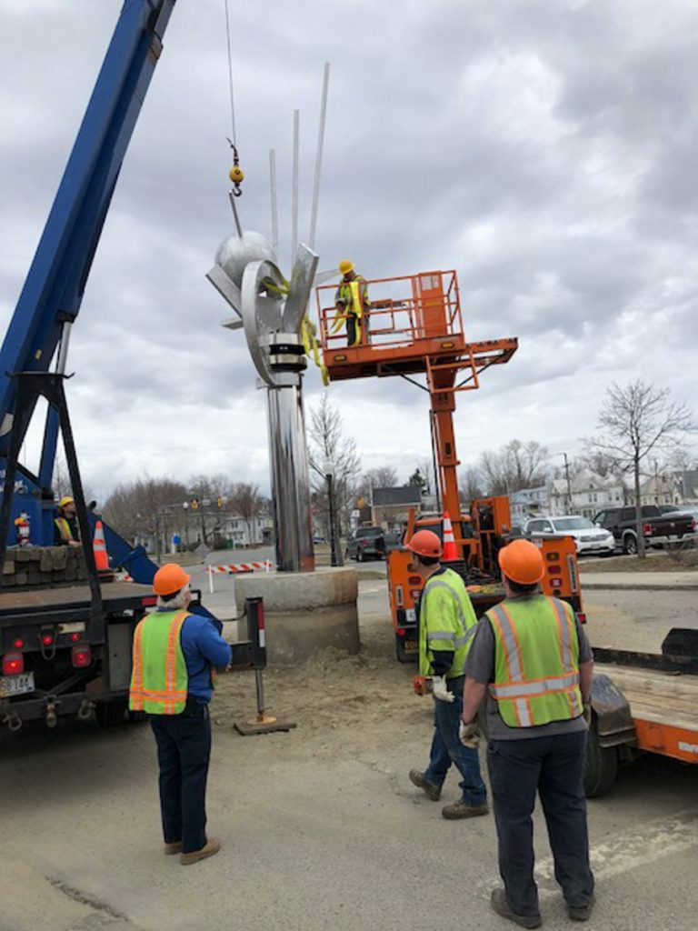 "Employees of The Cote Corp. and the Waterville Public Works Department prepare to remove the top part of ""The Ticonic"" sculpture Wednesday morning on The Concourse in Waterville. In the bucket is public works facility maintenance technician Mike Folsom."