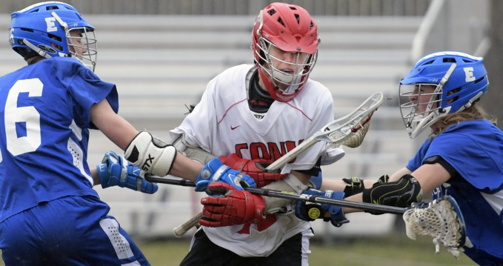 Cony's Micquais Baisuz runs between the defense of Erskine's Kyle Kirkpatrick, left, and Logan Poulin during a lacrosse match Wednesday in Augusta