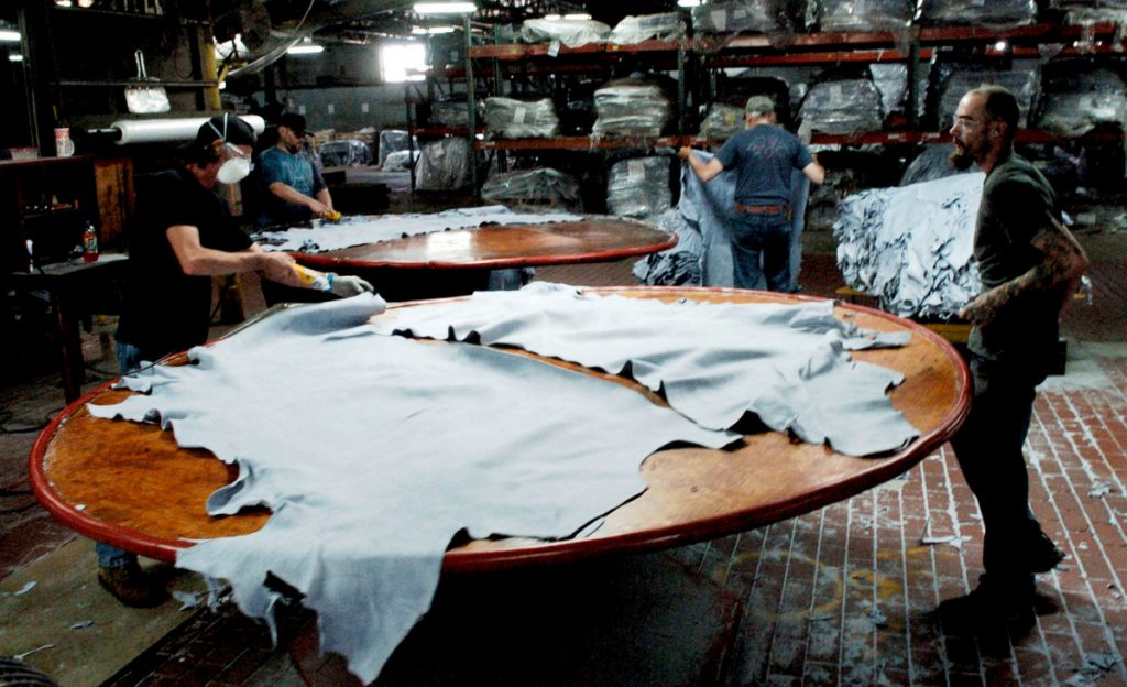 Employees at Tasman Leather Group work on July 20, 2016, at a station at the Hartland mill. The mill was a beneficiary of federal brownfields money in the past.