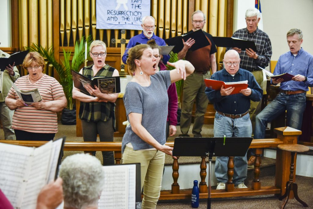 CODA Chorus director Joelle Morris, center, leads rehearsal Monday night in Winthrop. The chorus celebrates its anniversary with two concerts this Saturday at Hope Baptist Church in Manchester. The concert consists of pieces performed from every decade since its inception about 50 years ago.