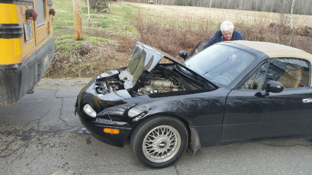 A school bus backed over a Mazda Miata sports car Friday on Industry Road in New Sharon. No injuries were reported.