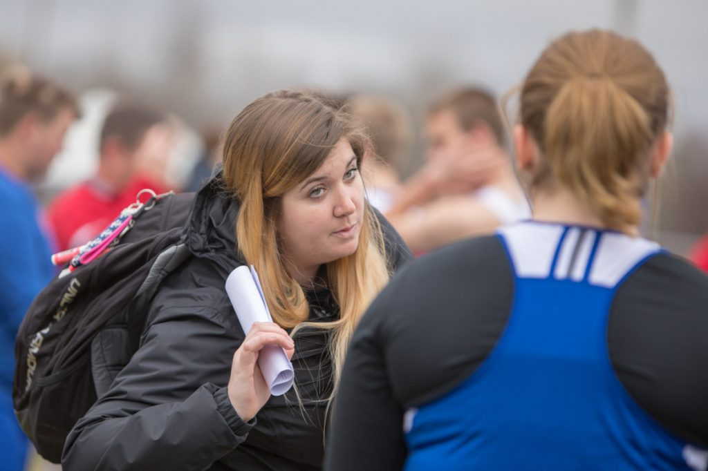 Photo by Jennifer Bechard   Erskine Academy throwing coach Meagan Hughes, sister of MCI thrower Allison Hughes, talks with one of her athletes at the Husky Throwdown on Saturday in Pittsfield.