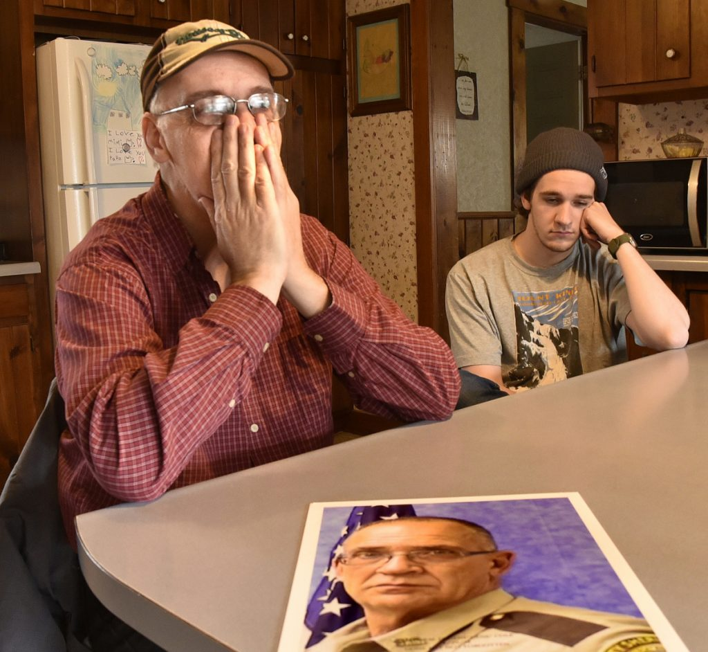 Tom Cole, left, brother of slain Somerset County Deputy Cpl. Eugene Cole, in the photograph, tries to regain his composure while talking about his brother in Skowhegan on Sunday. At right is his son Scott.