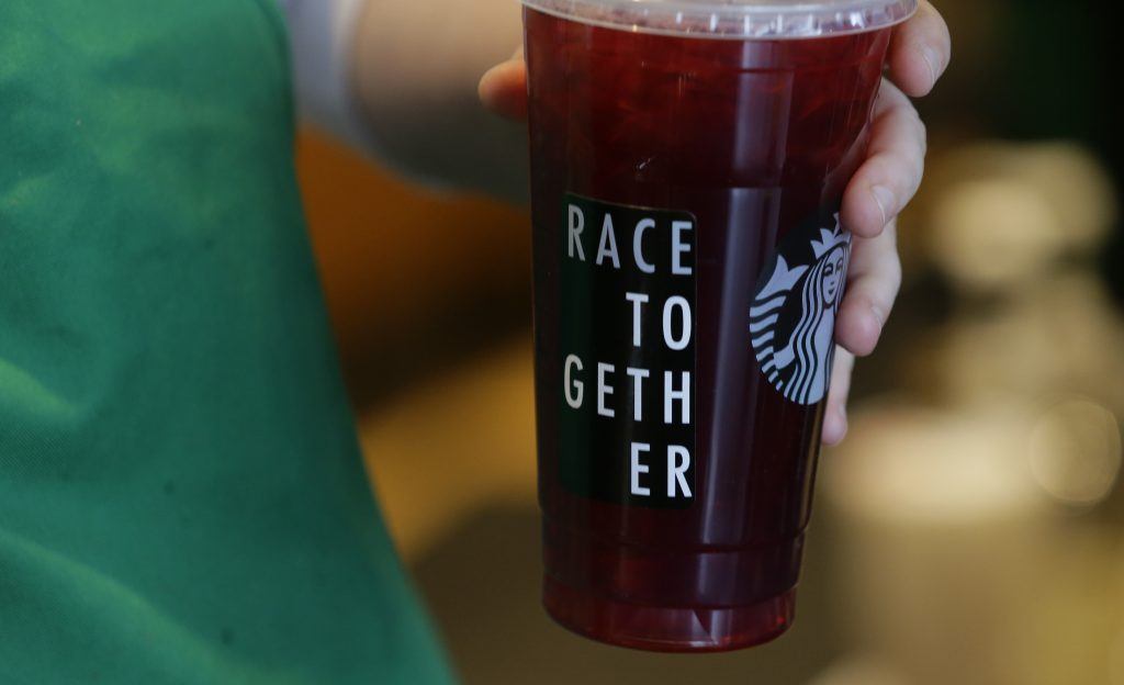 "A Starbucks barista holds an iced tea drink with a ""Race Together"" sticker on it on March 18, 2015, at a Starbucks store in Seattle. Three years ago, Starbucks was widely ridiculed for trying to start a national conversation on race relations by asking its employees to write the words ""Race Together"" on coffee cups. The initiative, though it backfired, was in line with the company's longstanding effort to project a progressive and inclusive image."