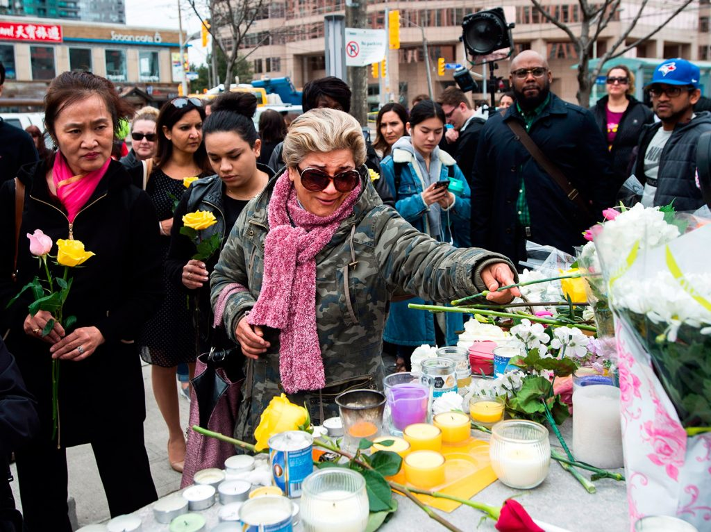 A tearful Ozra Kenari places flowers Tuesday at a memorial for the victims the day after a driver drove a van onto a crowded sidewalk in Toronto, killing 10 people.