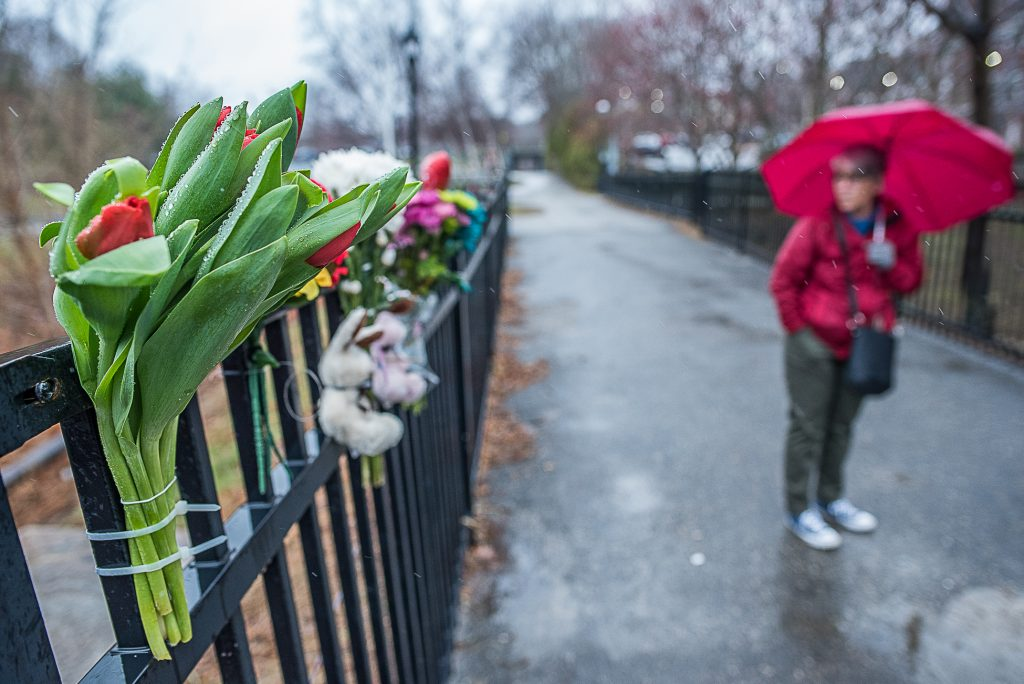 Linda Scott stands on the pedestrian bridge and looks at the tribute she organized Wednesday for two young brothers who fell into the Androscoggin River on Tuesday night.