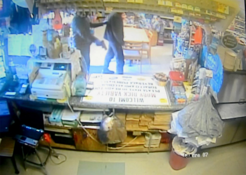 "An image taken from surveillance video Wednesday at the Moby Dick Variety Store in Old Orchard Beach shows the robber with a gun at the back of Ilias Sigkas, who was confronted while smoking outside and forced to enter the business. ""I was scared,"" Sigkas said."