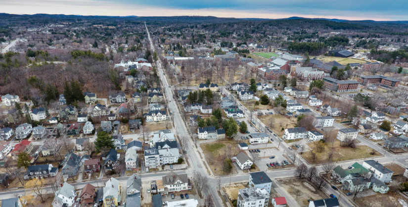 College Street runs down the center of the frame dividing much of the Bates College campus and neighborhoods mixed with families, elderly and young college students.