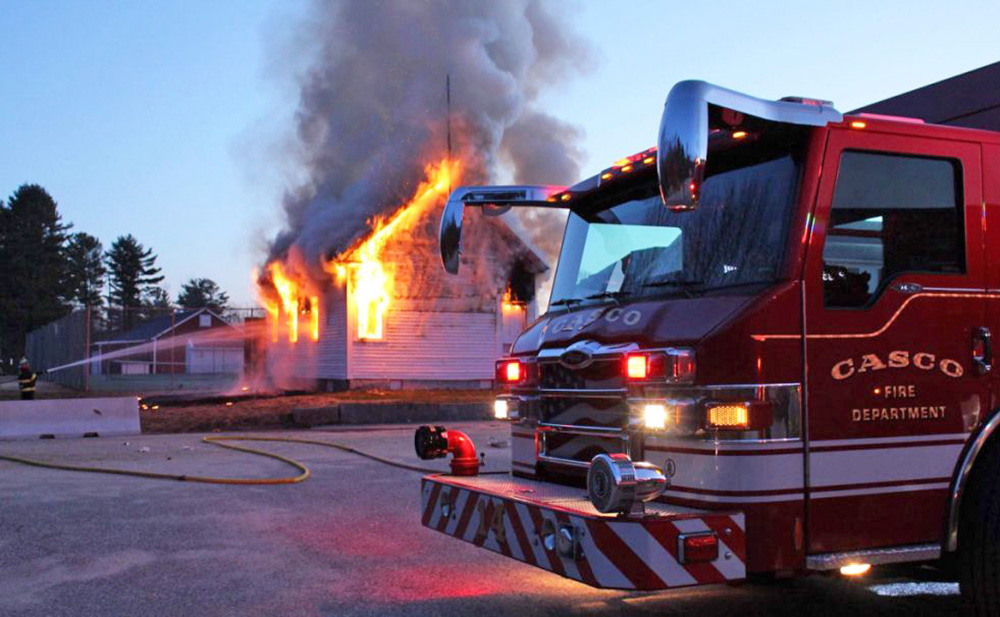 Firefighters battle the blaze at the Friends School House in Casco on Sunday.