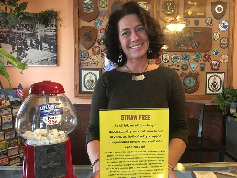 Cheri Siatras, who co-owns Joshua's Restaurant & Tavern in Brunswick, holds a sign announcing the decision to go plastic straw-free.