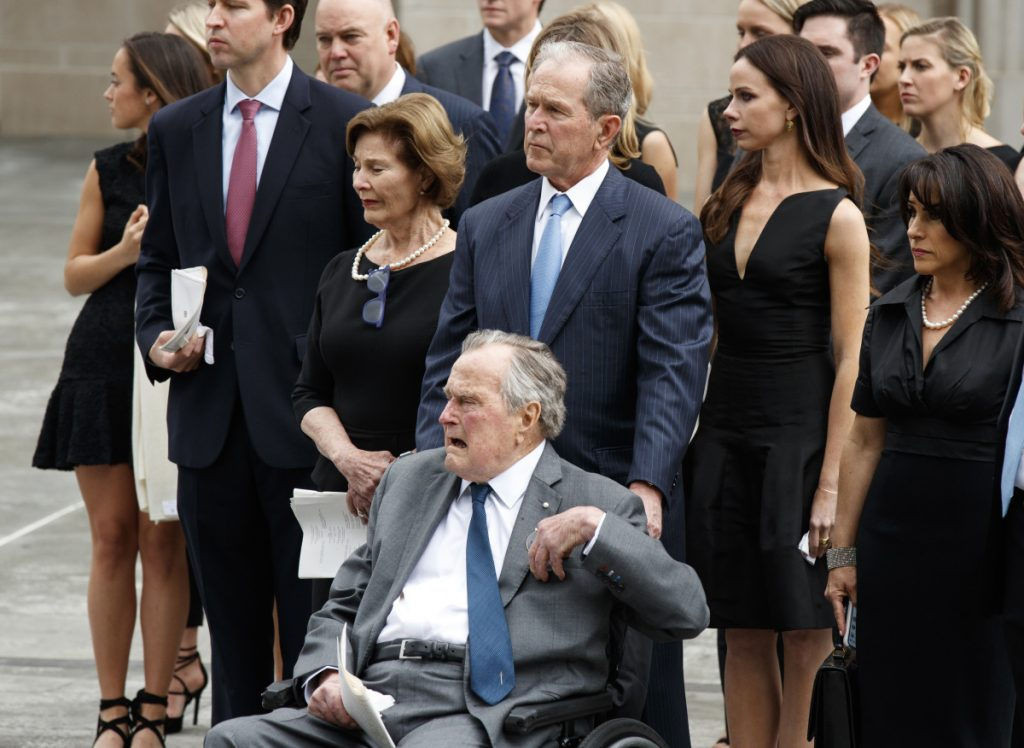 Former President George H.W. Bush, in wheelchair, his son former President George W. Bush, and other family members watch as the casket of former first lady Barbara Bush is loaded into a hearse at St. Martin's Episcopal Church in Houston on April 21.