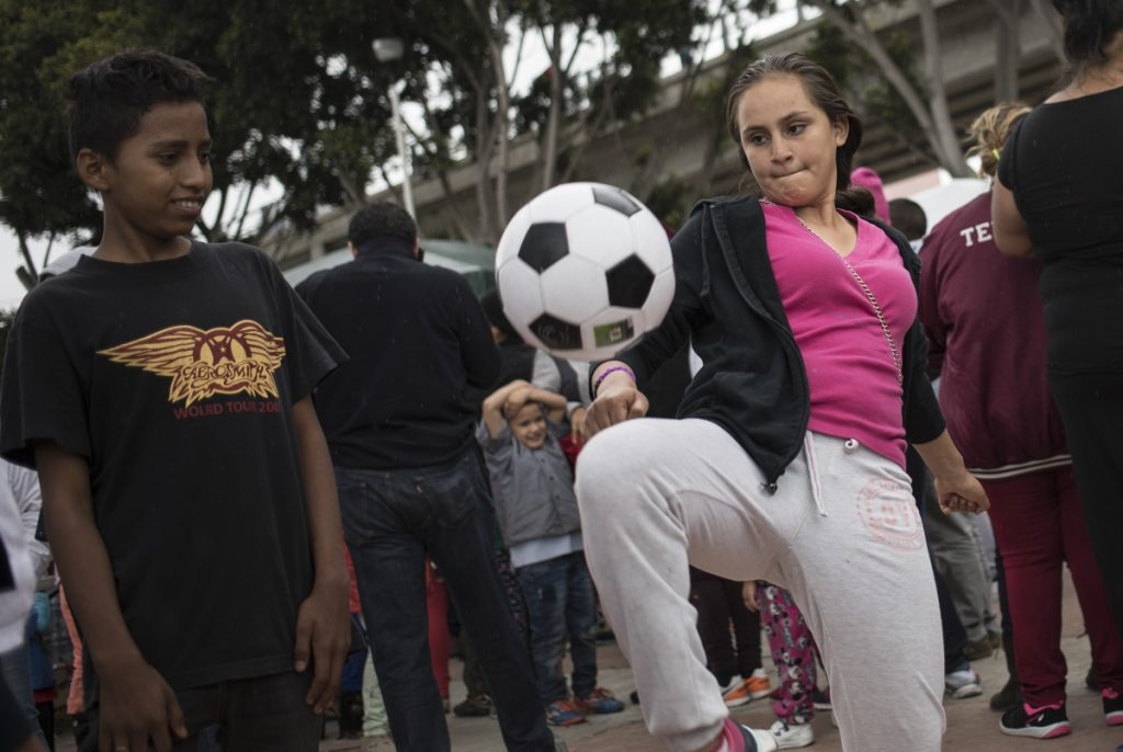 A migrant who traveled with the caravan of Central American migrants juggles a soccer ball where the group set up camp to wait for access to request asylum in the U.S.