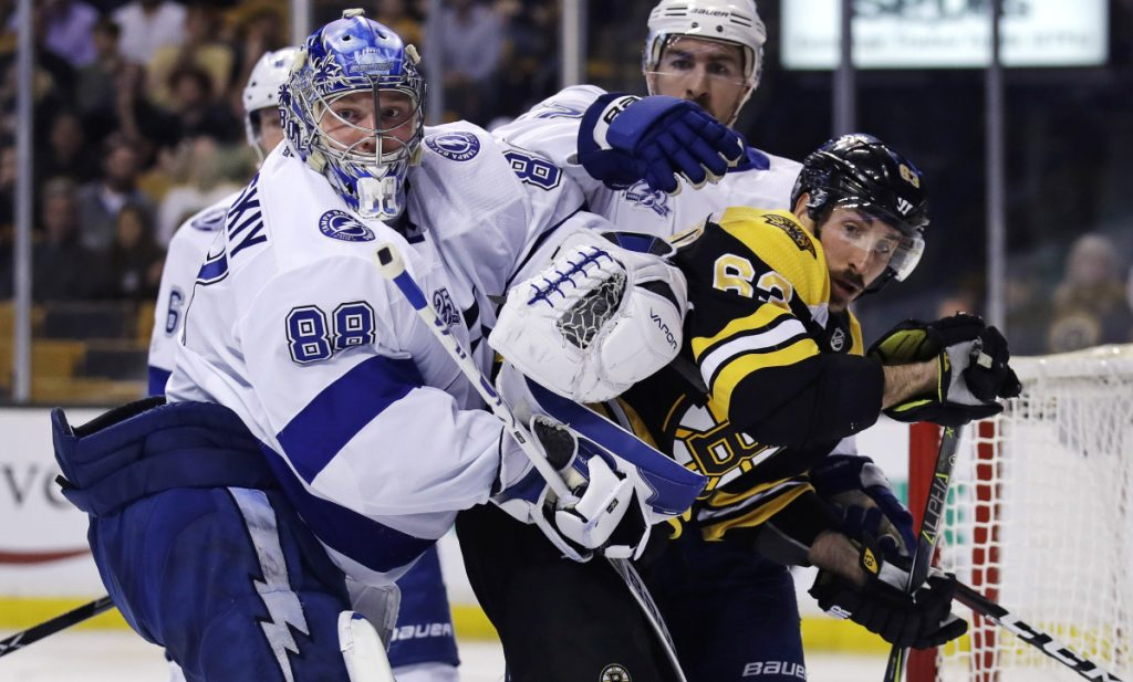 Tampa Bay Lightning goaltender Andrei Vasilevskiy tangles with Boston Bruins left wing Brad Marchand during the second period Wednesday night in Boston.