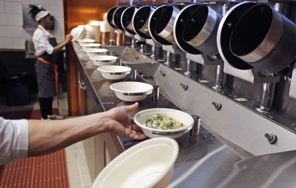 A worker lifts a lunch bowl off the production line at Spyce, a restaurant that uses an automated cooking process, after the eatery opened Thursday in Boston. Despite the high-tech machinery, the restaurant still employs plenty of humans.