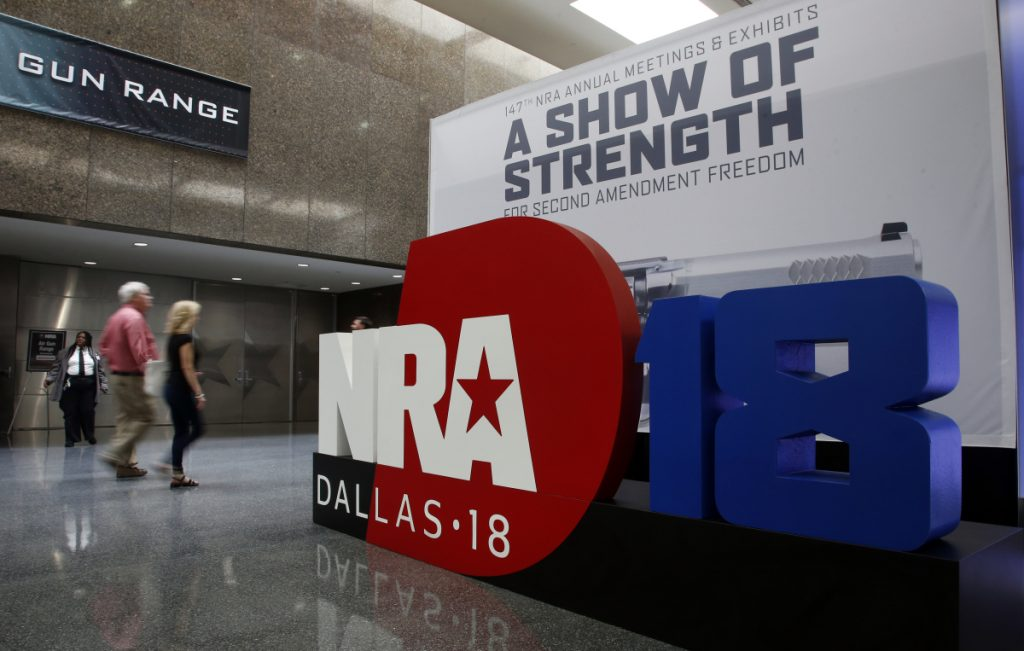 People walk past NRA convention signage at the Kay Bailey Hutchison Convention Center in Dallas. Several groups plan to protest outside the event, which runs through Sunday.
