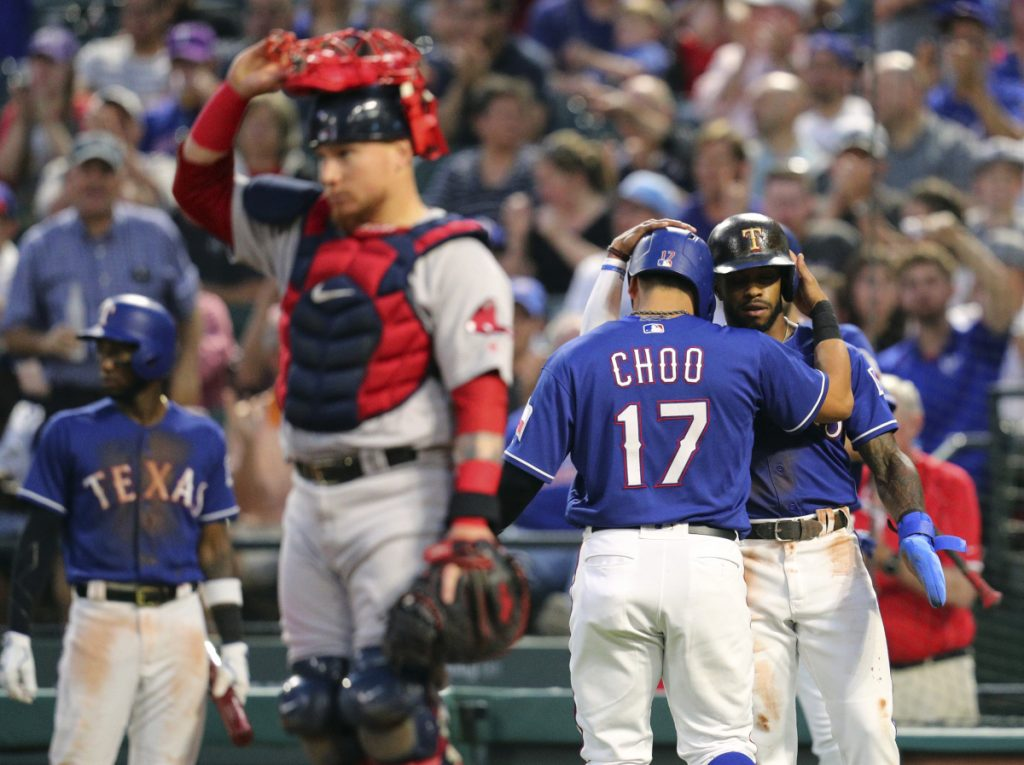 Boston catcher Christian Vazquez stands by the plate as Texas' Shin-Soo Choo, 17, and Delino DeShields, right rear, celebrate after scoring on Nomar Mazara's double during the third inning Thursday night at Arlington, Texas.