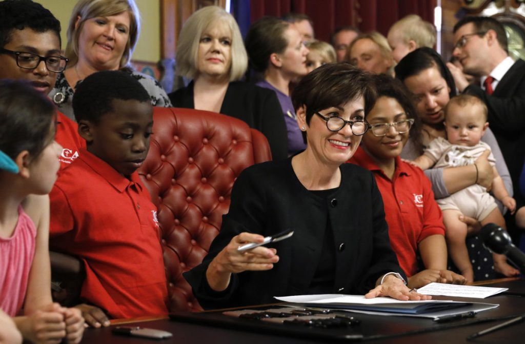 Iowa Gov. Kim Reynolds signs a six-week abortion ban bill into law during a ceremony Friday in Des Moines. The law gives Iowa the strictest abortion restrictions in the nation.