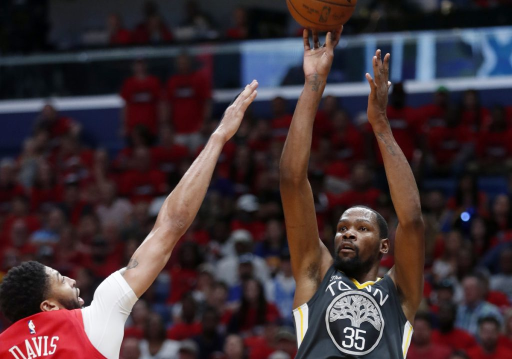 Kevin Durant, who finished with 38 points, lofts a shot over Anthony Davis of the New Orleans Pelicans in the first half of the Golden State Warriors' 118-92 victory Sunday. The Warriors will head home with a 3-1 series lead.