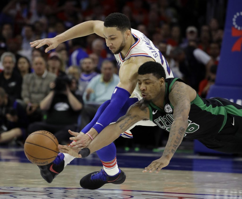 Boston's Marcus Smart, right, and Philadelphia's Ben Simmons chase after a loose ball during the first half of the 76ers' 103-92 win in Game 4 of their Eastern Conference semifinal series on Monday in Philadelphia.