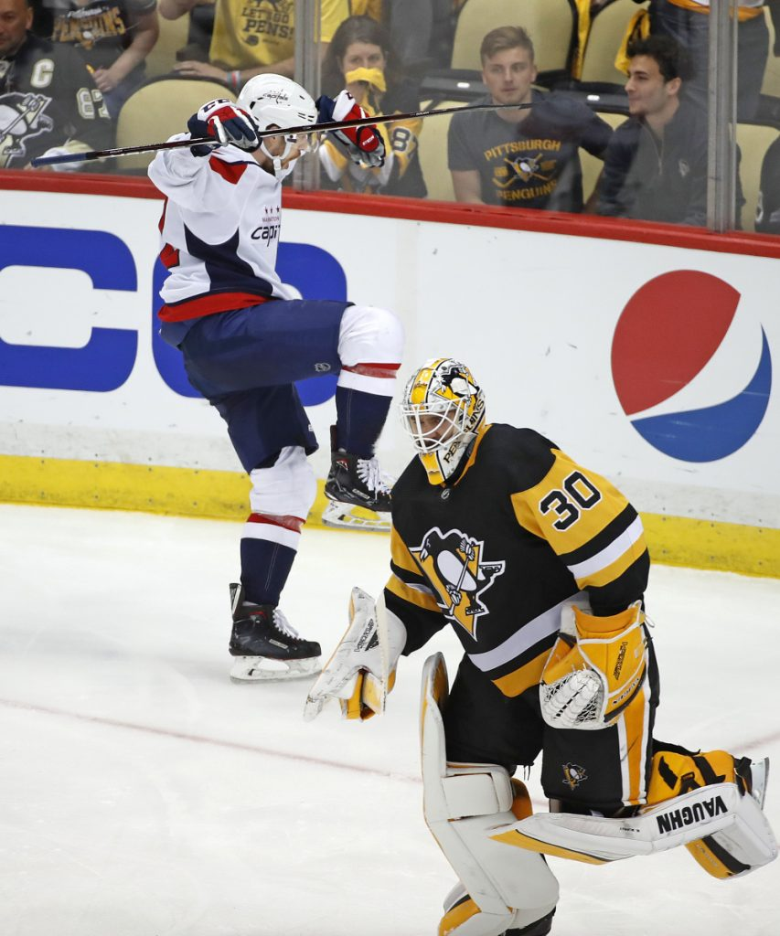Evgeny Kuznetsov of the Washington Capitals celebrates Monday night as Pittsburgh Penguins goaltender Matt Murray skates off after allowing the winning goal.