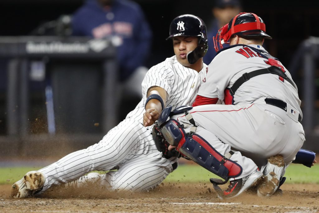 Boston catcher Christian Vazquez tags New York's Gleyber Torres out at home plate as Torres tried to score on Aaron Judge's seventh-inning, RBI single in a Tuesday's game in New York.