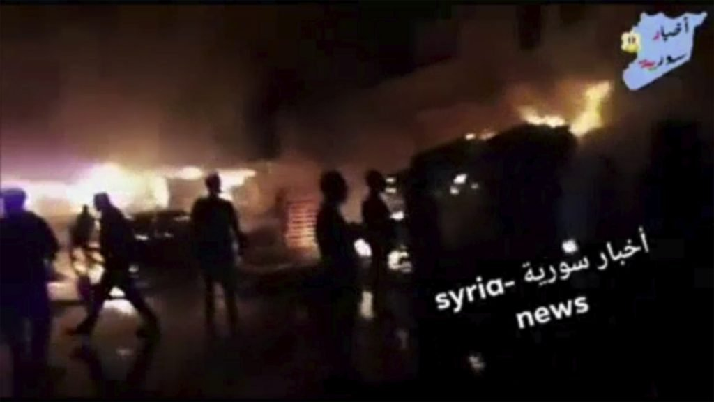 This image from video shows people standing in front of flames rising after an attack on an area known to have numerous Syrian army military bases, in Kisweh, south of Damascus, Syria, on Tuesday. In return, Iranian forces based in Syria fired 20 rockets at Israeli front-line military positions in the Golan Heights early Thursday.