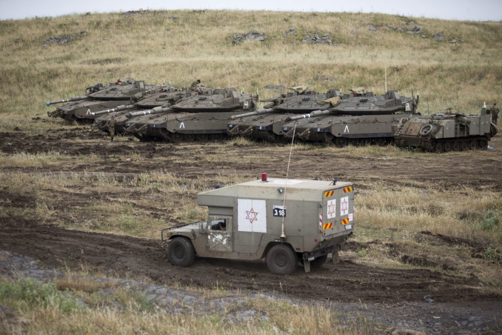 An Israeli military ambulance drives past tanks in the Israeli-controlled Golan Heights, near the border with Syria, on Thursday.