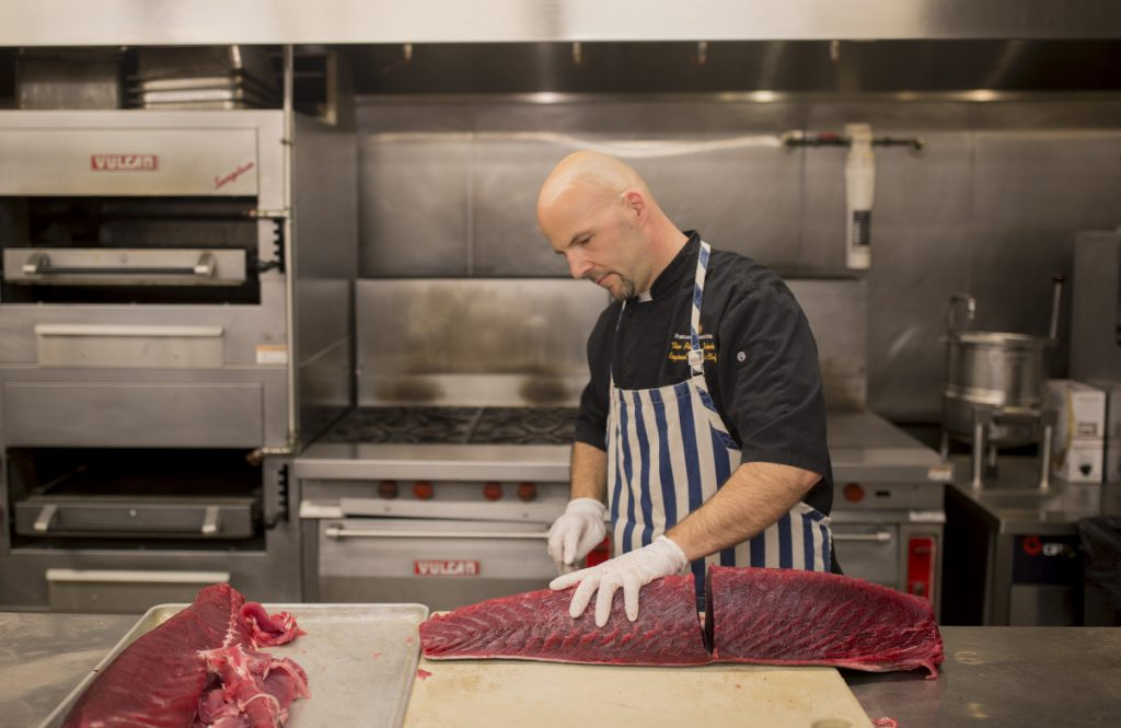 Tim Labonte, the executive regional chef for Maine Properties, breaks down tuna in the kitchen at BlueFin in the Portland Harbor Hotel. The restaurant is in the space formerly occupied by Eve's at the Garden.