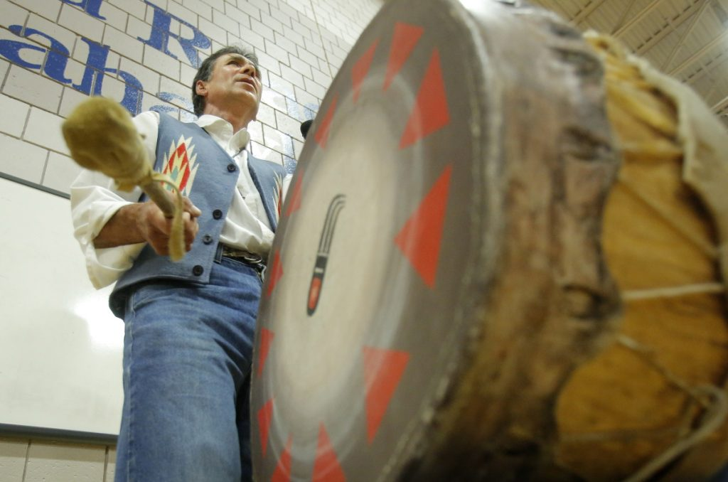 A member of the Penobscot Nation chants and beats a drum in 2013 at a Kennebunk school during a weeklong program about Native American culture and traditions. The University of Maine and the Penobscot Nation have signed an agreement to help preserve the tribe's cultural heritage.