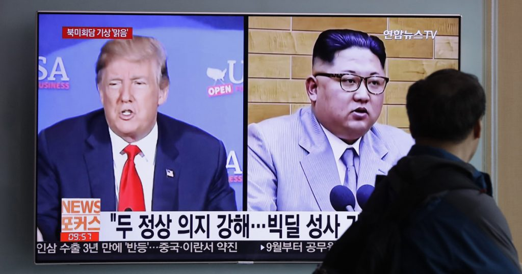 """A man watches a TV screen showing file footage of President Trump and North Korean leader Kim Jong Un with onscreen letters reading """"Summit between U.S. and North Korea, Forecast, Clear"""" on Friday in Seoul, South Korea."""