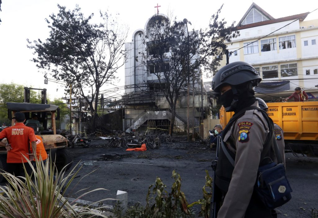 A police officer stands guard at one of the sites of church attacks in Surabaya, East Java, Indonesia, on Sunday. Suicide bombers on motorcycles and including a woman with children targeted Sunday Mass congregations in three churches in the country's second-largest city, killing at least seven people and wounding dozens in one of the worst attacks on the country's Christian minority, police said.