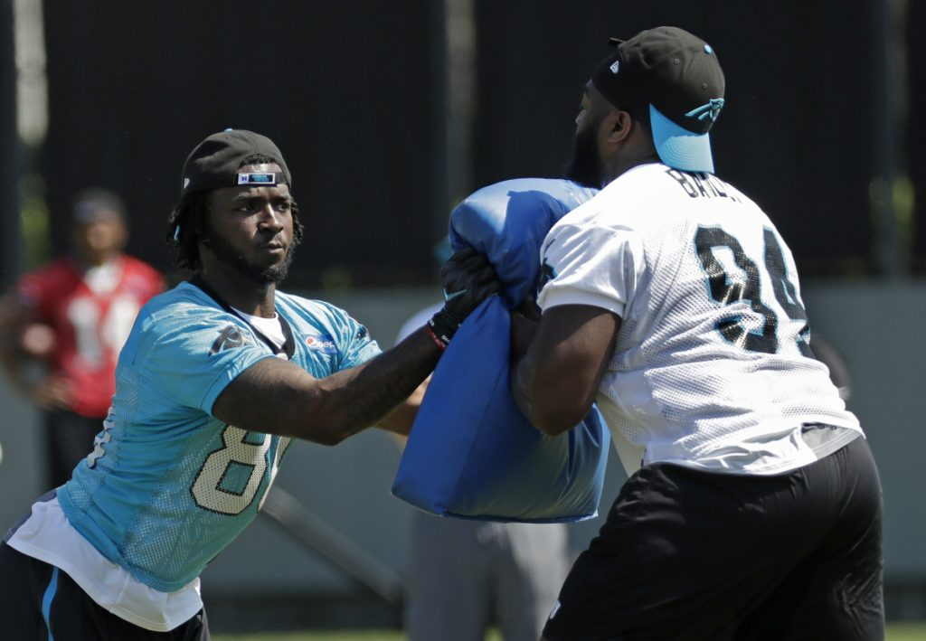 Carolina Panther Ian Thomas runs a drill against Sterling Bailey (94) during the team's rookie camp in Charlotte, N.C., on Friday. Sources say the team has been sold to hedge fund manager David Tepper.