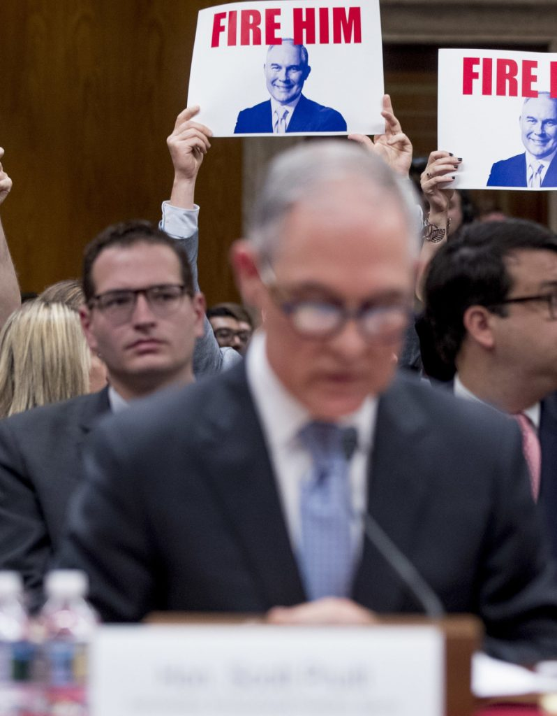 "Members of the audience hold signs reading ""Fire Him"" as EPA Administrator Scott Pruitt, center, testifies Wednesday before a Senate appropriations subcommittee."