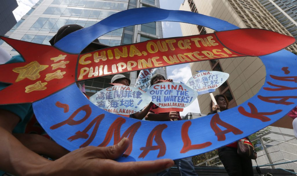 Protesters display placards during a rally at the Chinese consulate in the financial district of Makati city, east of Manila, Philippines.