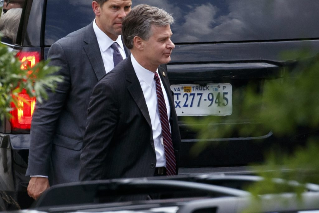 FBI Director Christopher Wray, foreground, leaves the White House after meeting Monday with President Trump amid reports that the agency had an informant who met several times with Trump campaign officials with suspicious contacts linked to Russia.
