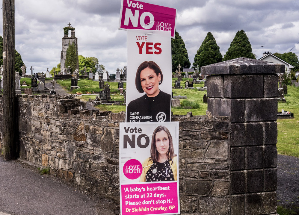 Signs for repealing and keeping Ireland's abortion ban can be seen outside a cemetery in Castlerea, Ireland.