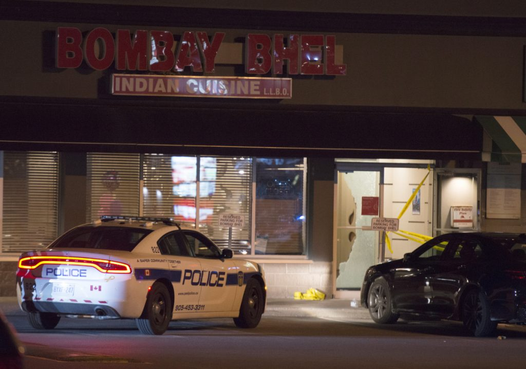 Police stand outside the Bombay Bhel restaurant in Mississauga, Canada, on Friday.