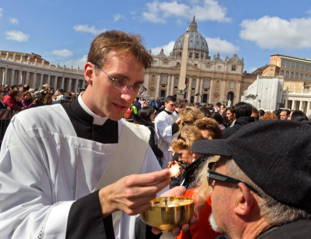 A priest delivers communion to the faithful in St. Peter's Square during the inauguration Mass for Pope Francis at the Vatican in 2013.
