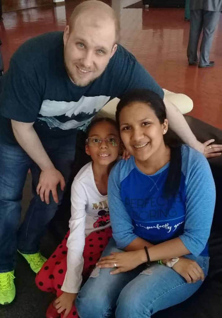 Joshua Holt poses for a photo with his wife, Thamara Caleno, and her daughter at the airport in Caracas, Venezuela, on Saturday.