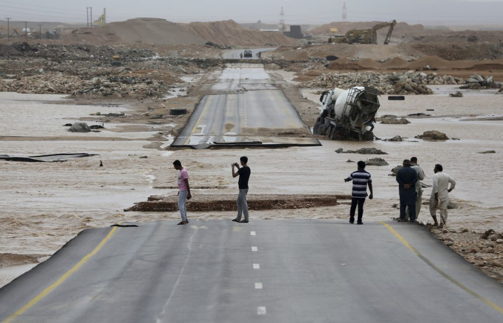 People visit a road cut by floodwaters after Cyclone Mekunu in Salalah, Oman, on Saturday. The cyclone blew into the Arabian Peninsula, drenching Oman and Yemen with rain and cutting off power lines.