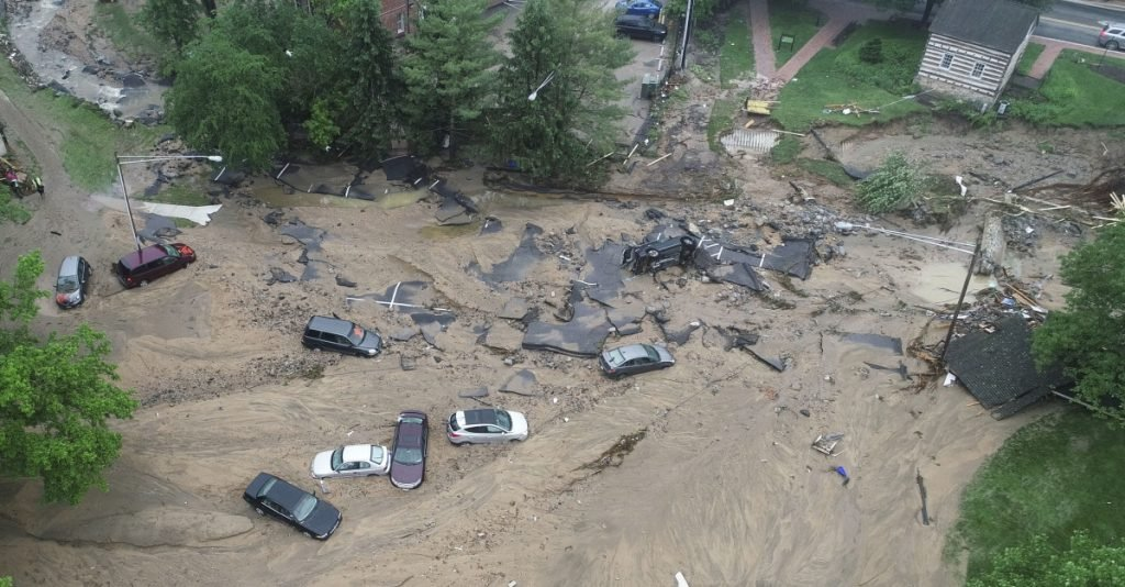 This image made from video provided by DroneBase shows vehicles swept by floodwaters near the intersection of Ellicott Mills Drive and Main Street in Ellicott City, Md., Monday.