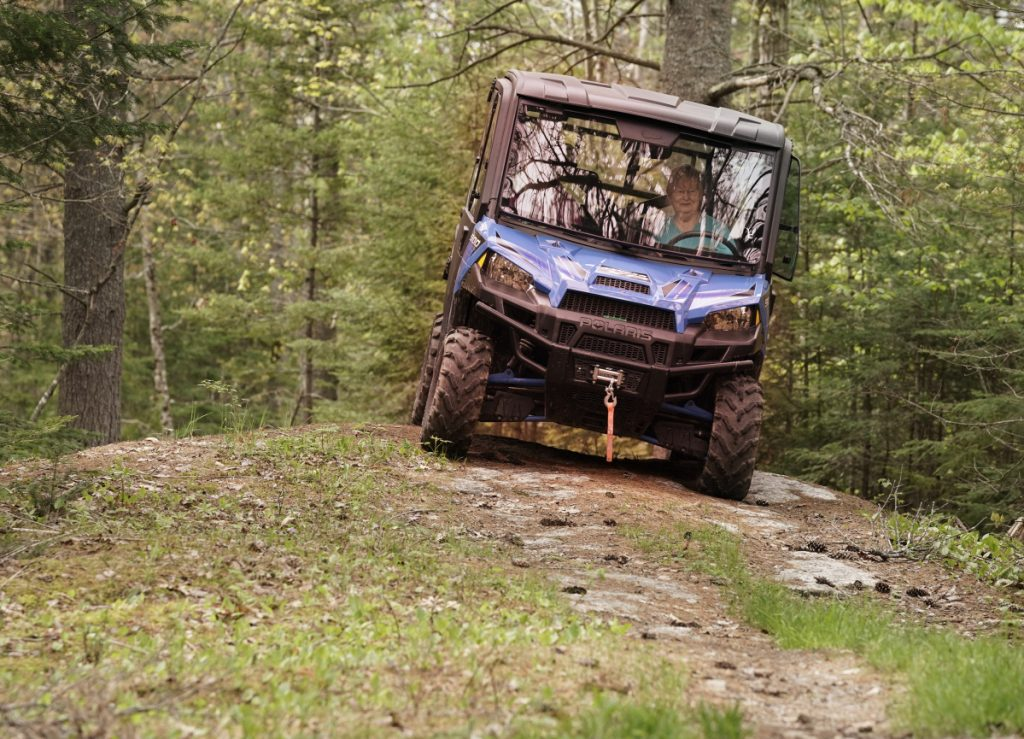 Alicia Cote drives a side-by-side on her family's property in Bowdoin this month. The popular vehicles are larger than ATVs and can take a toll on the land, which could lead to a diminished trail system if private landowners close their property to the off-road vehicles.