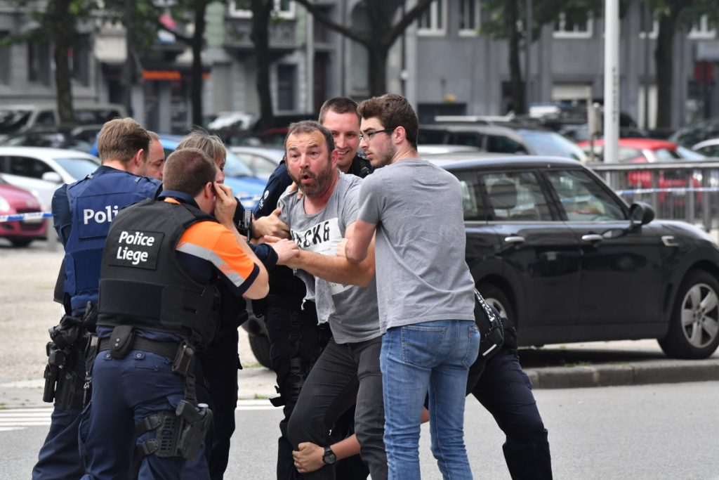 Police try to calm a man at the scene of the shooting in Liege, Belgium.